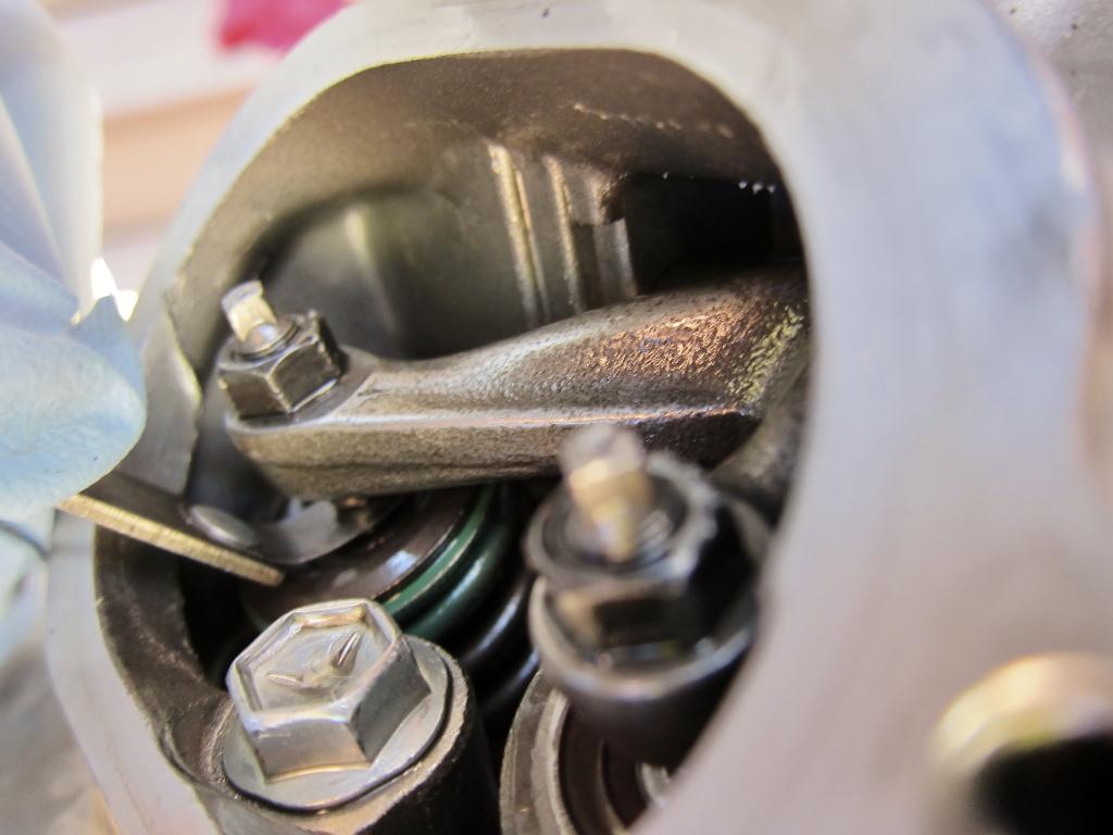 Sliding the feeler gauge between the valve stem and rocker arm