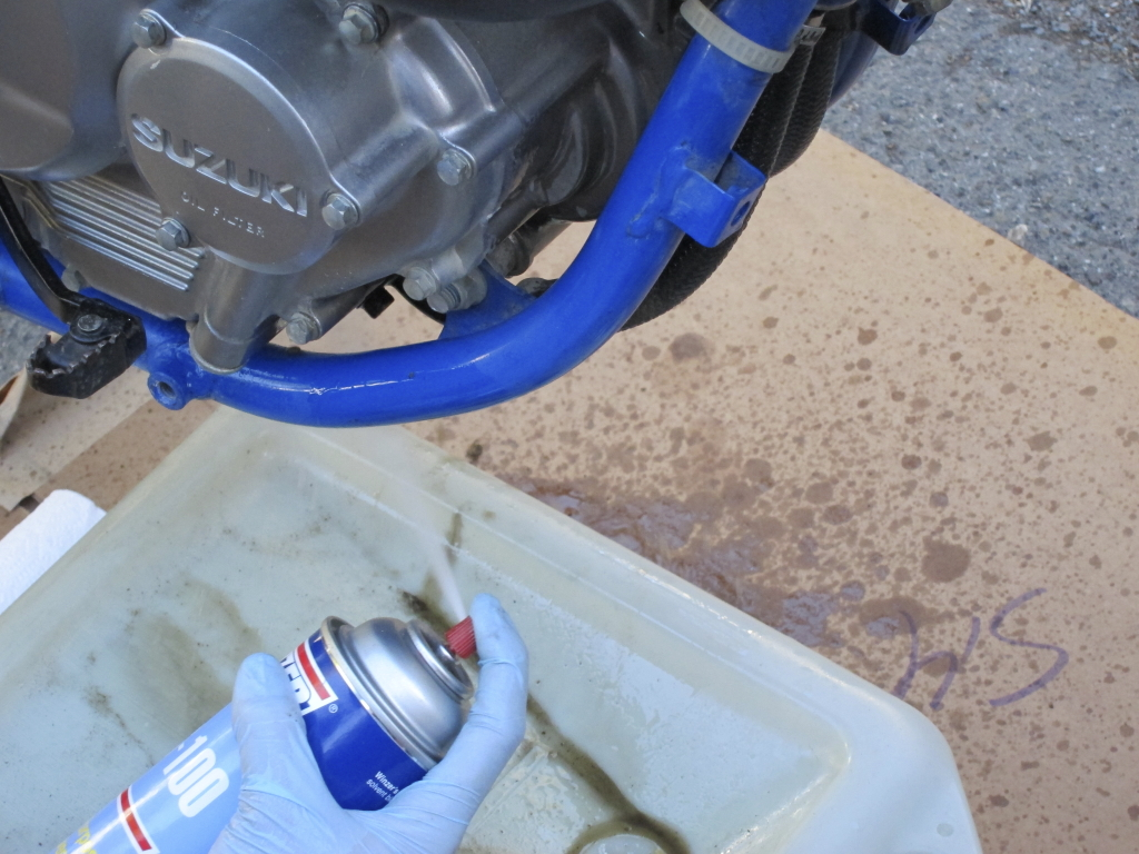 Spraying cleaning solvent on oily surfaces