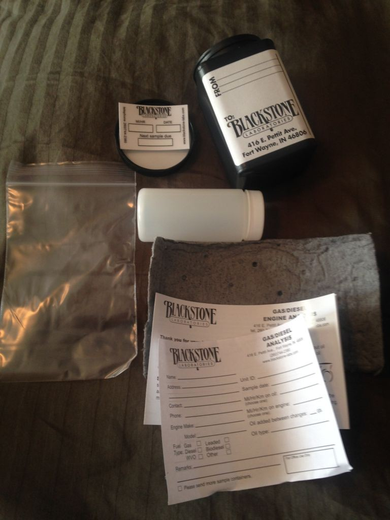 Contents of the oil testing kit: Outer bottle, inner oil sample bottle, ziploc for the inner bottle, absorbent cloth to wrap around inner bottle, report sheet, and window decal